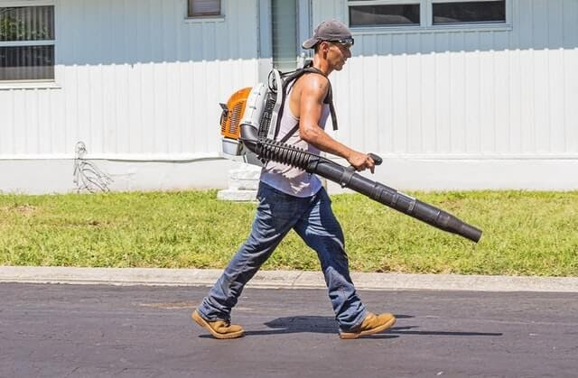 man in white tank top and blue denim pants with leaf blower 162564 1